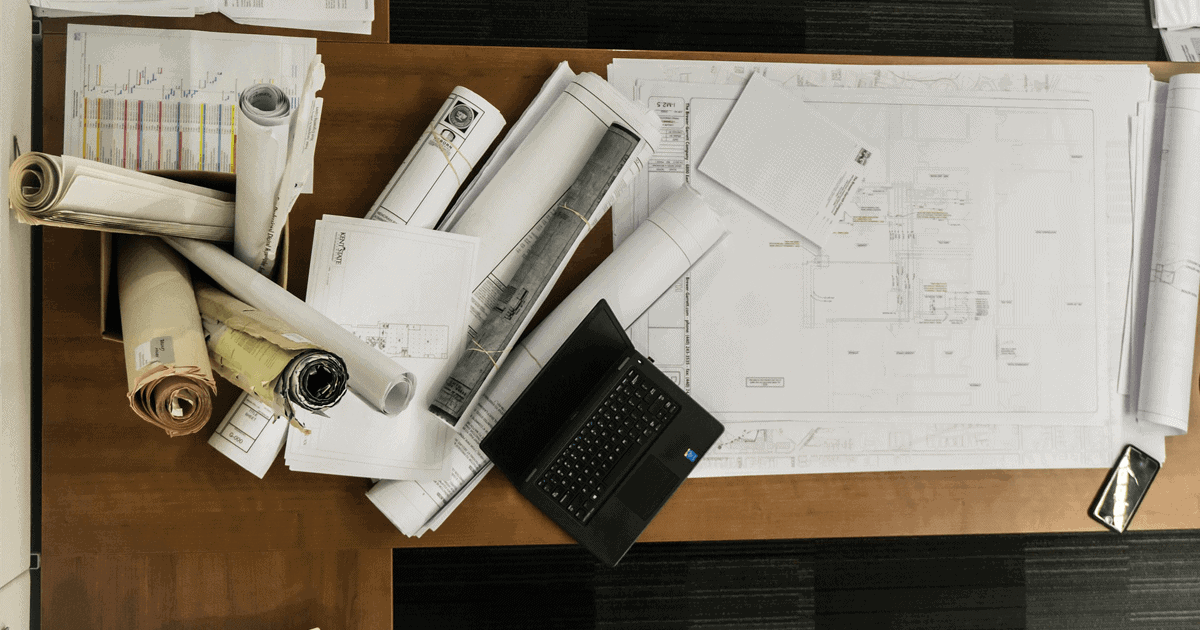 Skrivebord med papirruller, pc og plantegninger for arkitekter