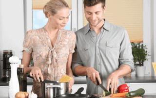 Kvinne og mann som lager middag på kjøkkenet