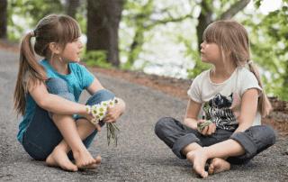 En jente i blå t-shorte og en jente i hvit t-skjorte sitter og snakker