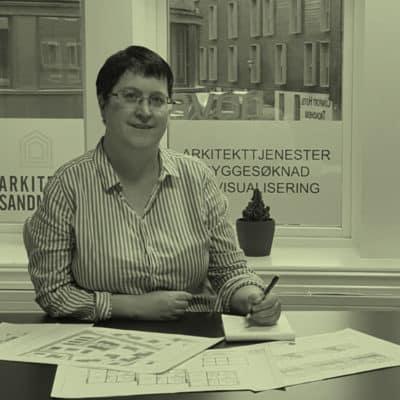 Arkitekt i stripete skjorte sitter foran et vindu og skisserer