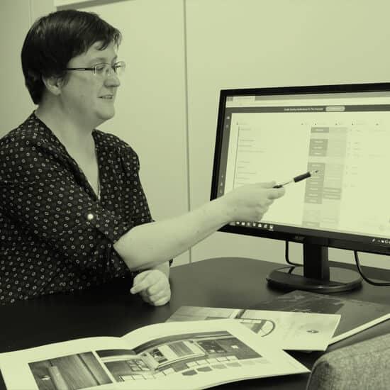 Arkitekt Marianne Sandmark peker på en pc skjerm med innsyn i et prosjekt