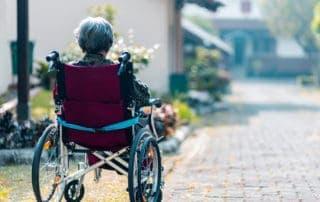 eldre kvinne i rød rullestol foran en bolig