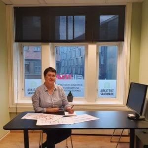 Arkitekt Marianne Sandmark sitter ved et skrivebord og skisserer