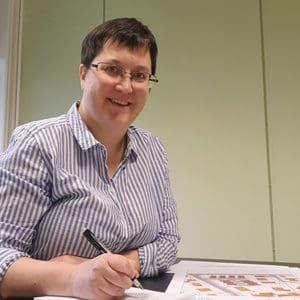Arkitekt i stripete skjorte sitter ved et skrivebord og skisserer