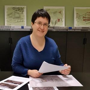 Arkitekt Marianne Sandmark sitter og skisserer på plantegninger med blyant og tusjer